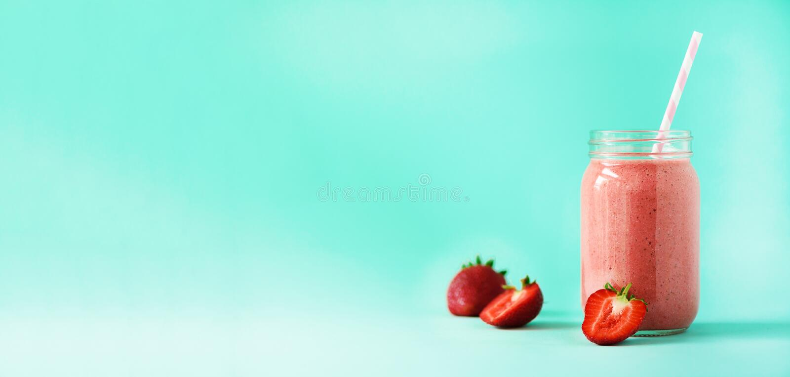 Bottle with vegan strawberry smoothie on blue background with copy space. Banner. Summer food concept, vegan diet. Pink royalty free stock photography