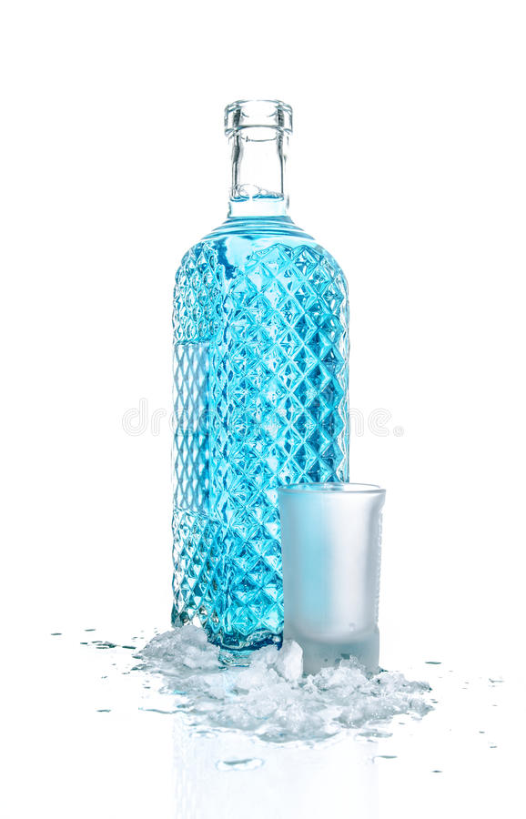 Bottle of vodka with wineglass and ice stock photo
