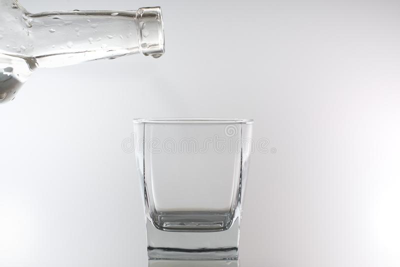 From the bottle, water or alcohol is poured into the glass. There is a drop on the bottle. stock images