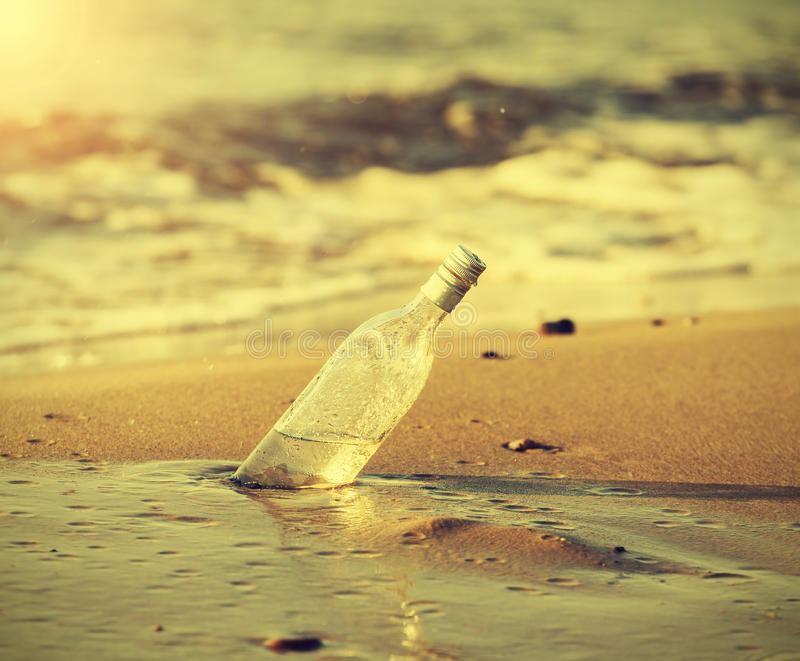 Bottle in water on beach at sunset, retro instagram effect. Bottle in water on beach at sunset, retro instagram vintage effect royalty free stock image