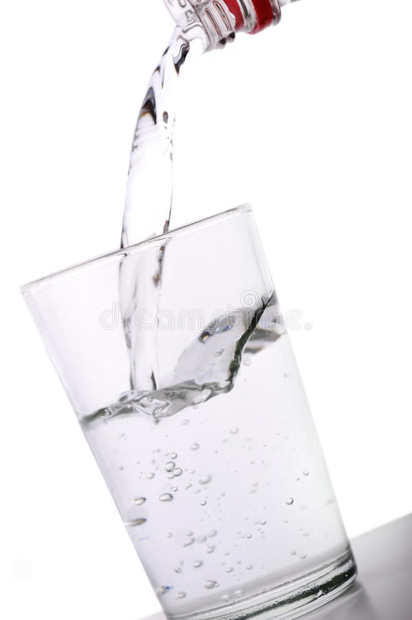 Bottle water into a blue glass royalty free stock photography