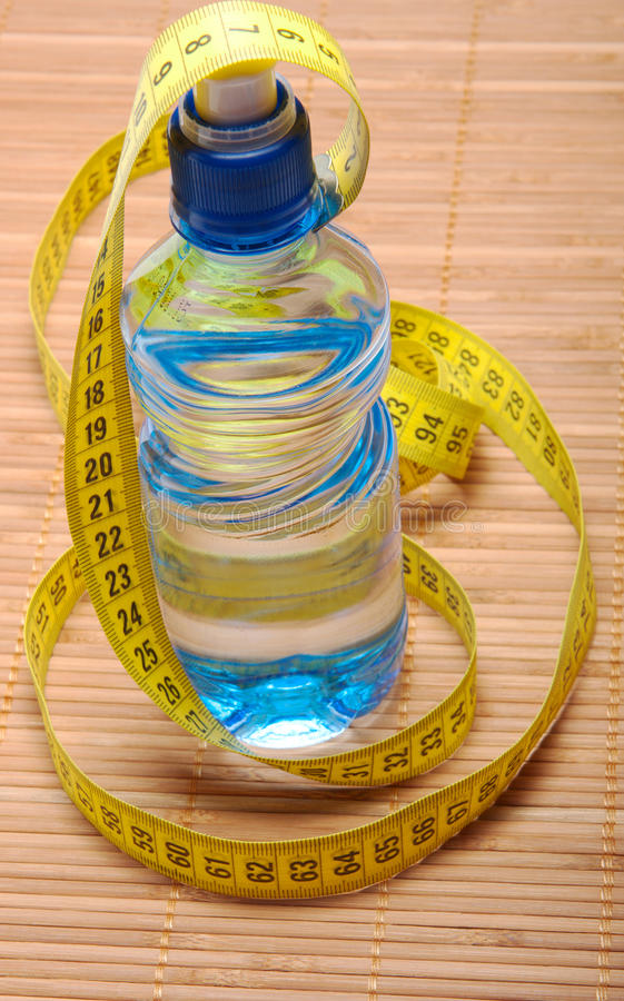 Bottle with water with centimeter tape stock image