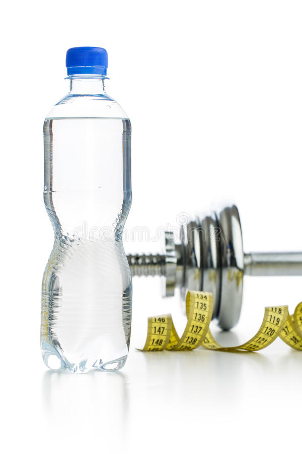 Bottle water and dumbbell. Bottle water and dumbbell isolated on white background royalty free stock photo