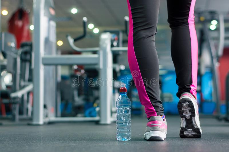 A bottle of water near the feet of the girl. A bottle of water near the feet of the girl in the background of the gym. Light background stock photos