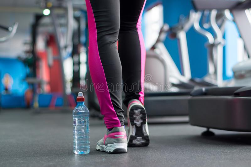A bottle of water near the feet of the girl. A bottle of water near the feet of the girl in the background of the gym. Light background royalty free stock image