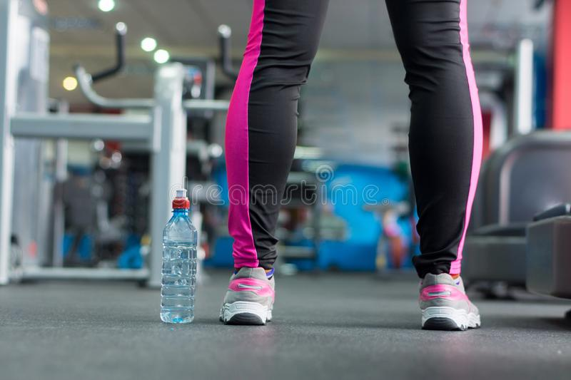 A bottle of water near the feet of the girl. A bottle of water near the feet of the girl in the background of the gym. Light background royalty free stock photography