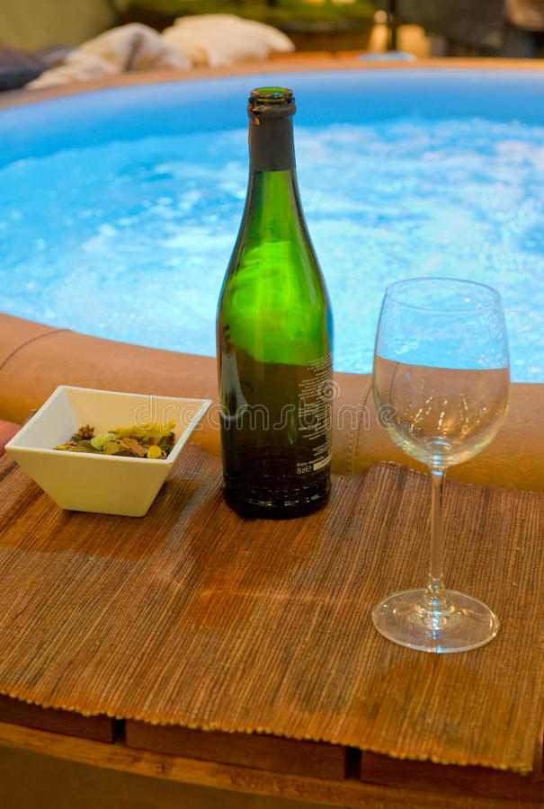 Bottle at a whirlpool. Champagne bottle on the edge of a whirlpool stock image