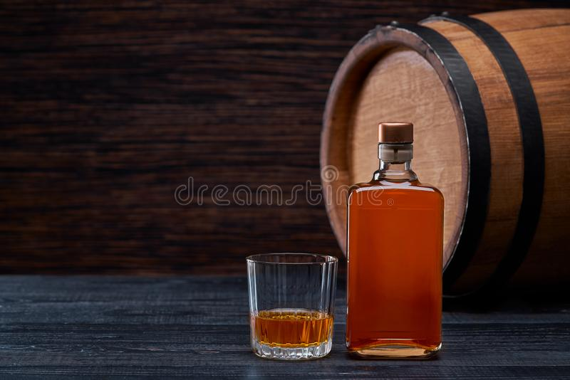 Bottle of whiskey on a black wooden in oak barrels. Studio shot royalty free stock photography