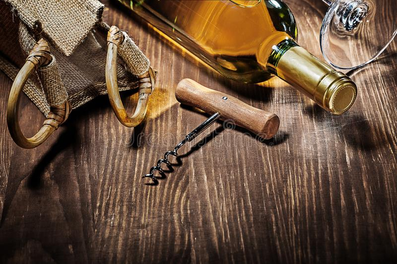 Bottle of white wine burlap bag corckscrew glass royalty free stock image