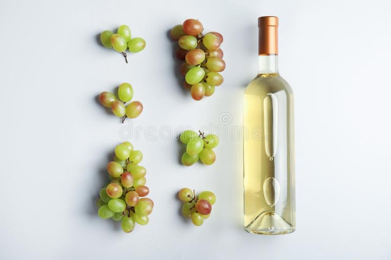Bottle with white wine and fresh ripe juicy grapes on light background stock image