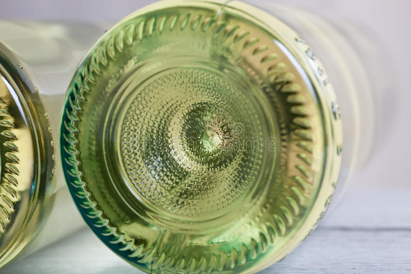 Bottle of white wine viewed from underneath. Lying on its side showing the domed shape and pattern on the clear glass with an iridescent effect from the wine stock photo