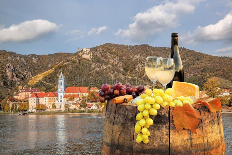 Bottle of wine on barrel with Durnstein village in Wachau, Austria royalty free stock photo