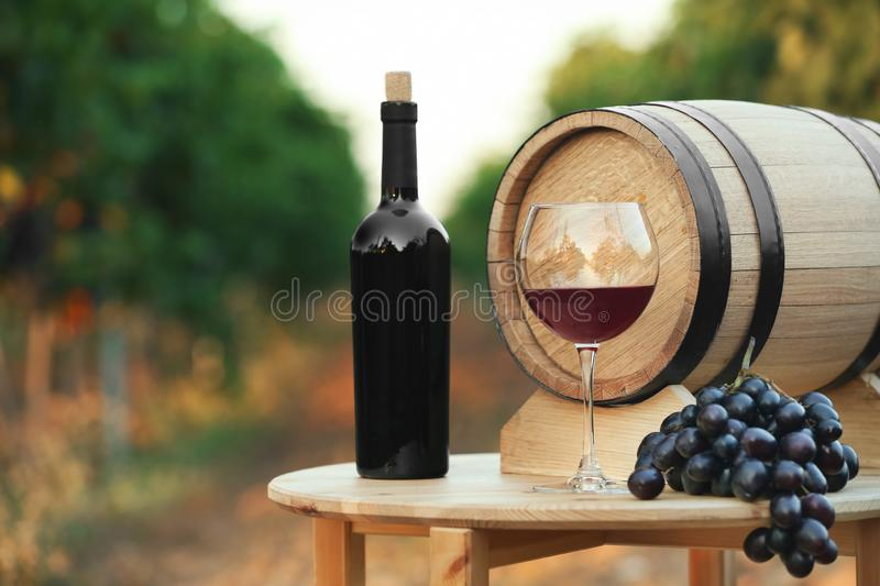 Bottle of wine, barrel and glass on wooden table royalty free stock photo