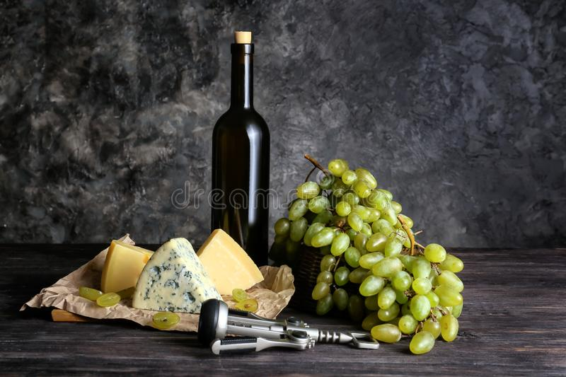 Bottle of wine with cheese and ripe grapes on wooden table royalty free stock photography