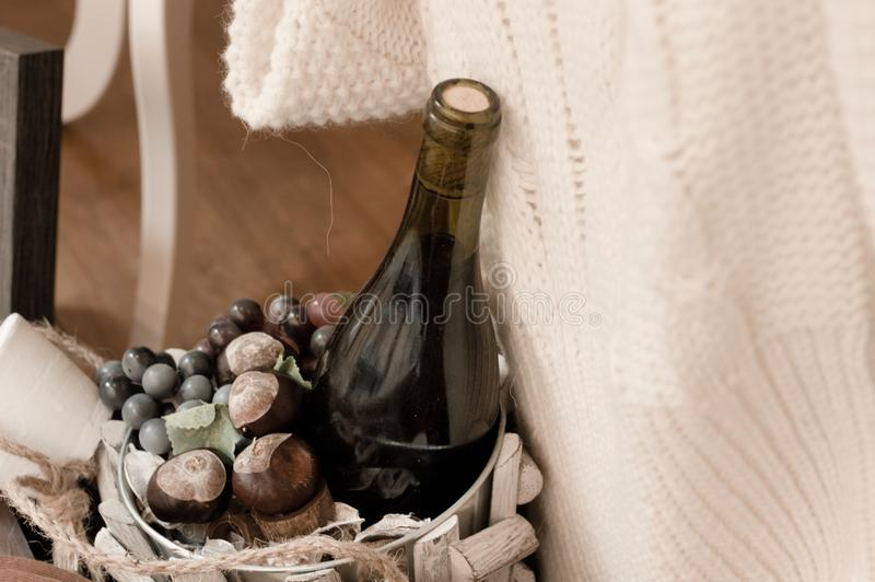 A bottle of wine with chestnuts into a wooden basken and a white pullover stock photos