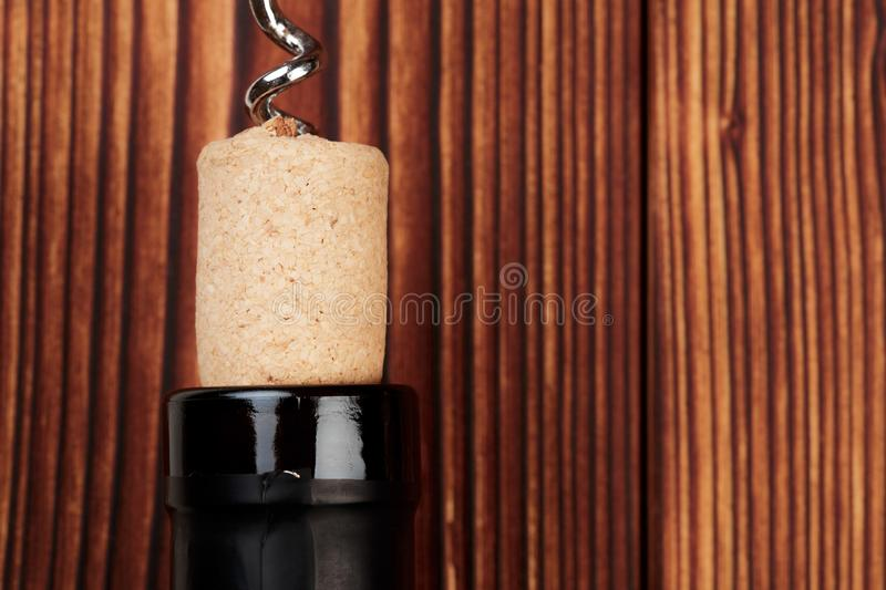Bottle of wine and cork and corkscrew on wooden table - image stock images