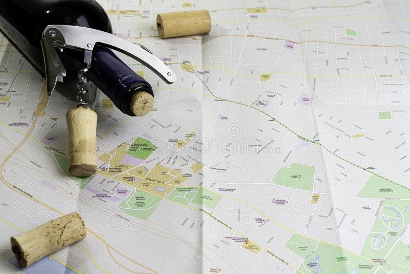 Bottle of wine and corks on map for route planning. Corkscrew opener stock photo