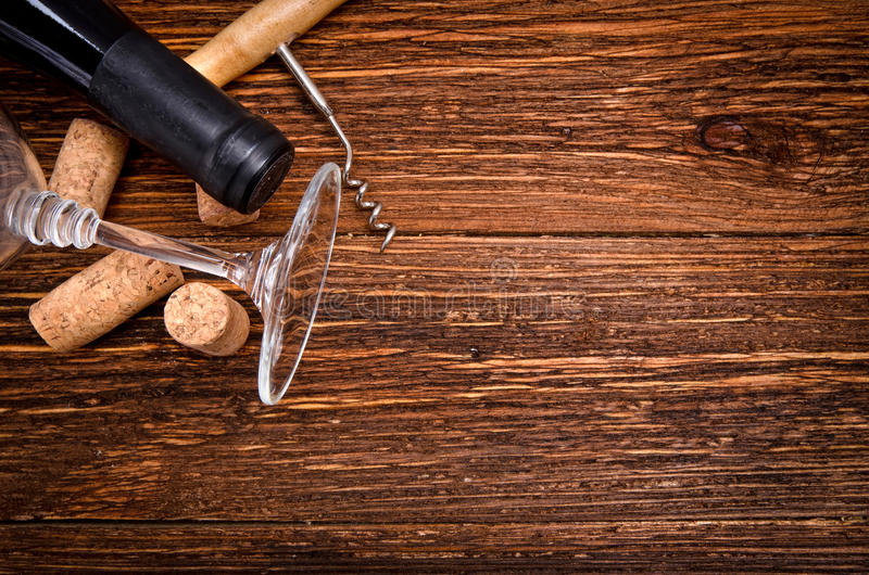 Bottle of wine, corkscrew and corks on wooden table. Background stock photo