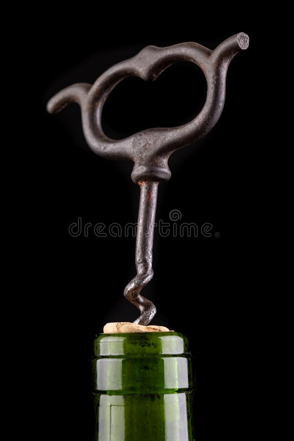 A bottle of wine and a corkscrew on a dark table. Opening good wine with a corkscrew stock images