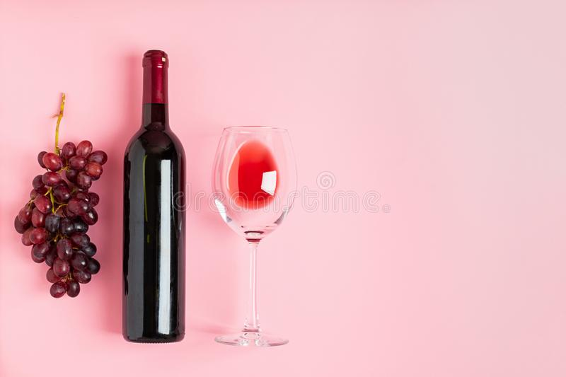 A bottle of wine an empty glass of a bunch of grapes on a gentle pink background. Minimalism. Top view flat layout royalty free stock images