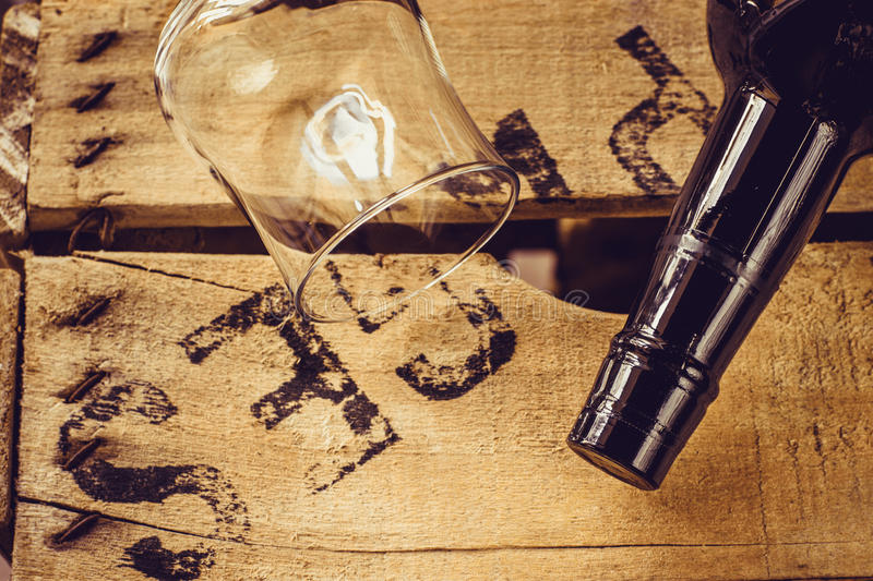 Bottle of wine and an empty wineglass on an aged wood box, top view, selective focus royalty free stock photography