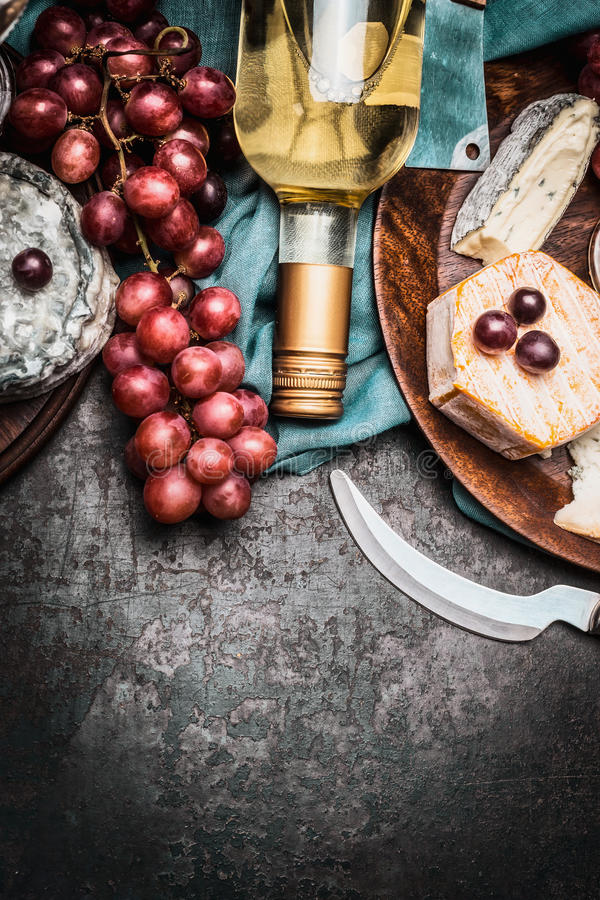 Bottle of wine with fine cheese and grape on dark rustic background, top view royalty free stock photos