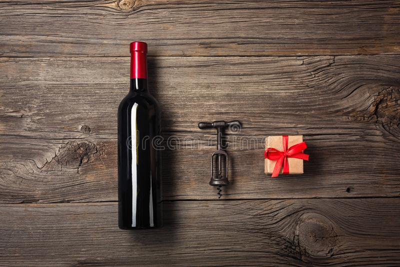 Bottle of wine with wine glass and gift box on wooden background. Top view with copy space for your text royalty free stock images
