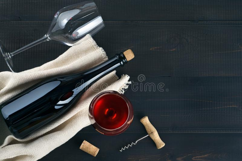 Bottle, wine glasses and corkscrew on dark table royalty free stock photography