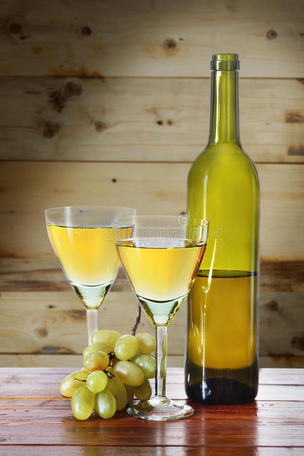 Bottle of wine and grape bunches on wooden surface