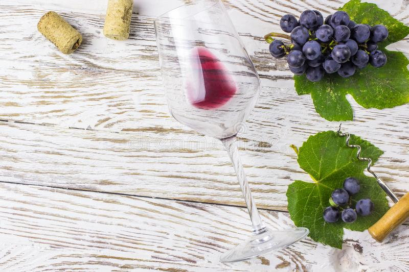 Bottle of wine, grapes and corks on wooden background royalty free stock image