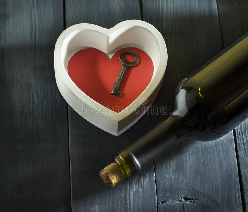 Bottle of wine with hearts Valentine`s Day. In the old blue wooden background. With copy space stock photos