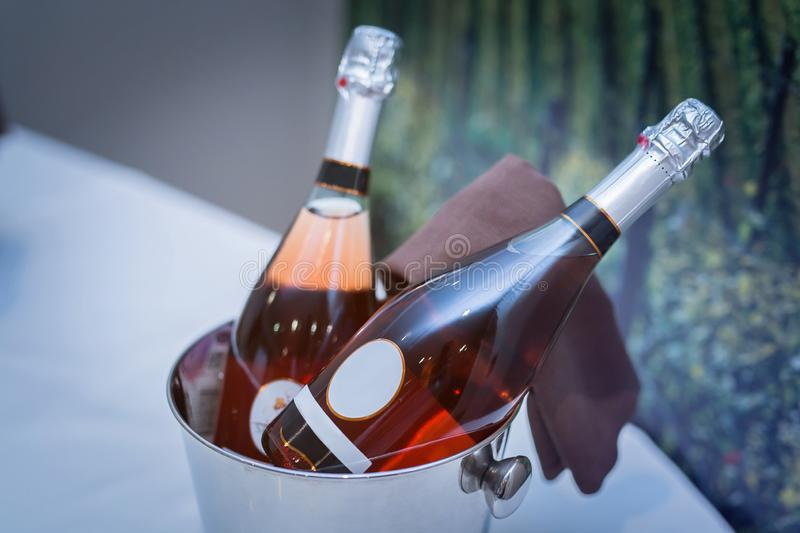 A bottle of wine lies in a bucket of ice on the table next to the glasses with drinks white royalty free stock photos