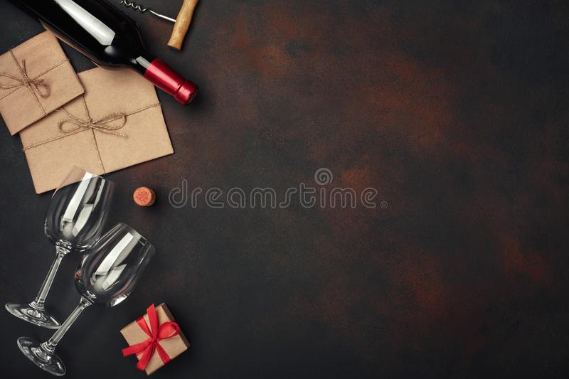 Bottle of wine, two glasses, gift box, envelope, corkscrew and corks, on rusty background top view stock photo