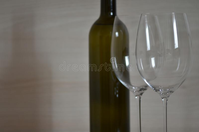 Bottle of wine and wine glass stemware in the simple interior. Of the apartment stock image