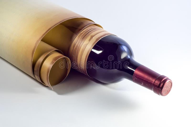 Bottle of wine wrapped in old paper scroll. On a light background stock photography