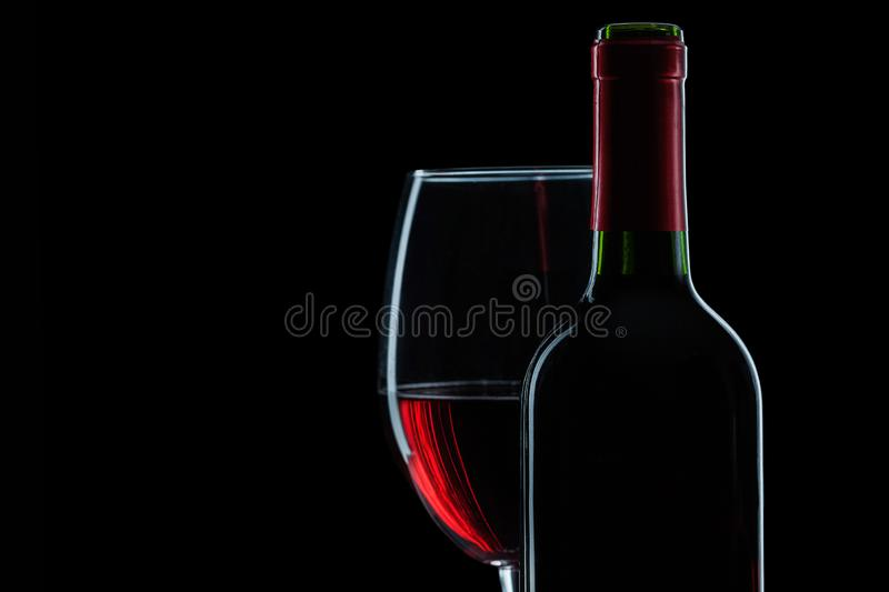 Bottle and wineglass with red wine on black background close up view stock image