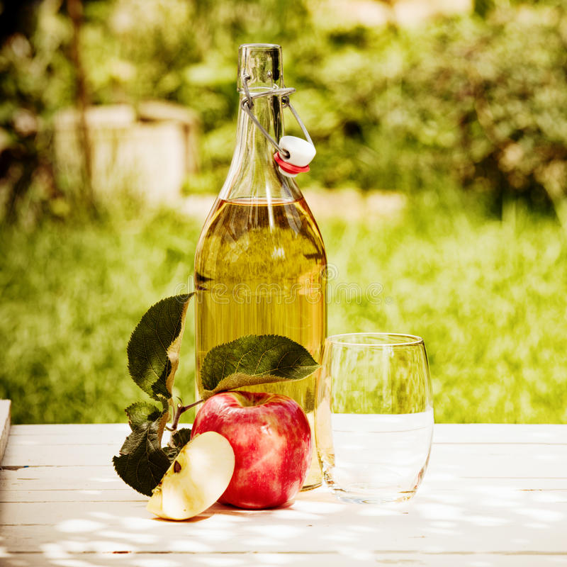 Bottled fresh apple juice served in the garden. With a juicy red apple and glass under the shade of a tree royalty free stock photo