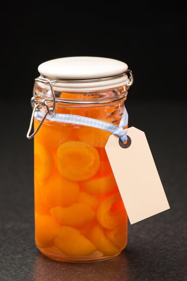 Bottled Fruit. Bottled apricot halves in glass preserve jar with label stock photos