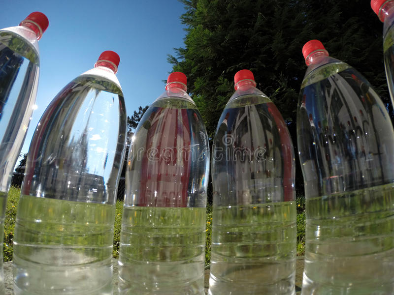 Bottled Water. Against a background of green nature royalty free stock image