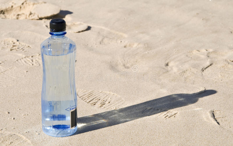 Bottled water on the beach. Single bottled water on the beach royalty free stock photography