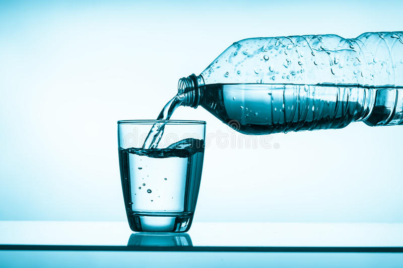 Bottled water and a glass royalty free stock image