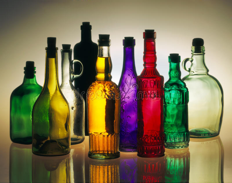 Bottles. Nine bottles of different sizes and colors stock photos