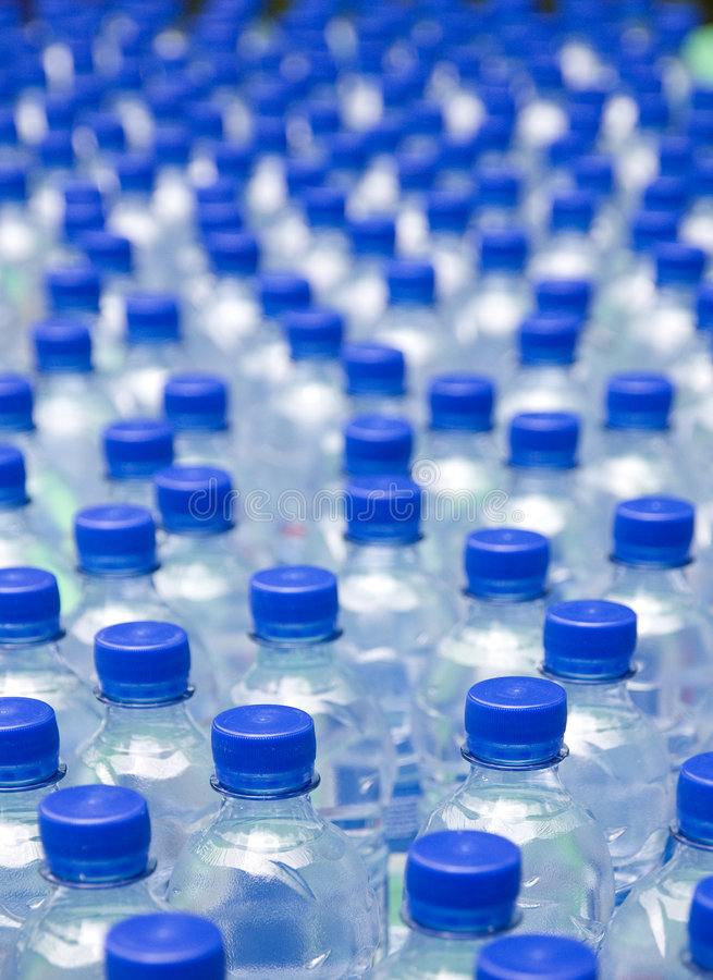Bottles. Water bottles with blue cups, shallow DOF