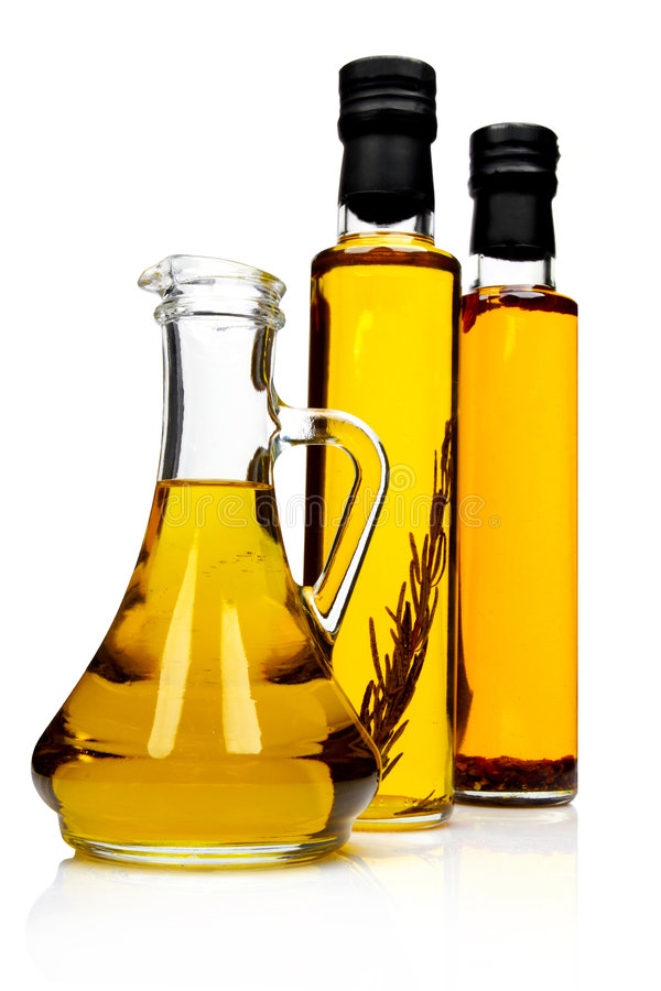 Bottles of aromatic olive oil. Bottles of aromatic olive oil with rosemary, chilli pepper and pure olive oil royalty free stock photo