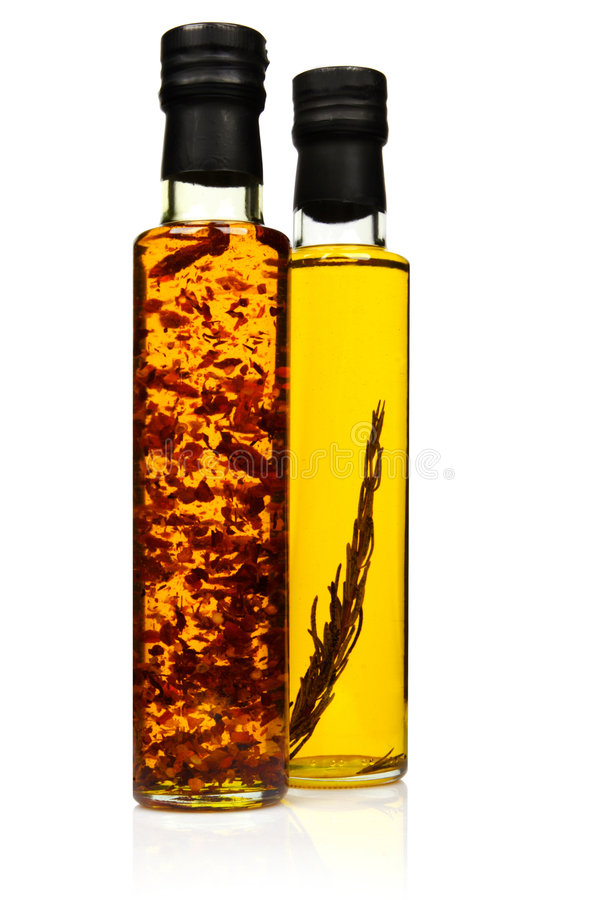Bottles of aromatic olive oil. Bottles of aromatic olive oil with rosemary and chilli pepper royalty free stock photo