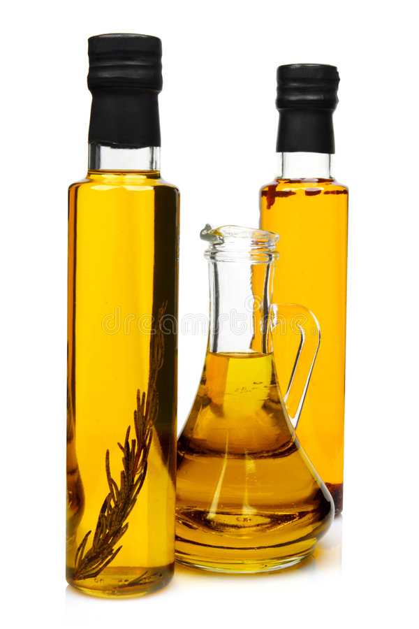 Bottles of aromatic olive oil. Bottles of aromatic olive oil with rosemary, chilli pepper and pure olive oil royalty free stock images