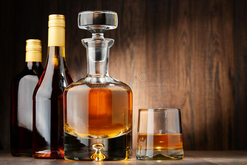 Bottles of assorted alcoholic beverages and glass of whisky. Composition with bottles of assorted alcoholic beverages and glass of whisky stock image