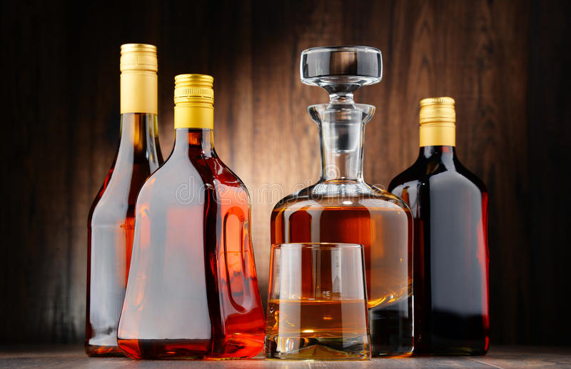 Bottles of assorted alcoholic beverages and glass of whisky. Composition with bottles of assorted alcoholic beverages and glass of whisky stock photos
