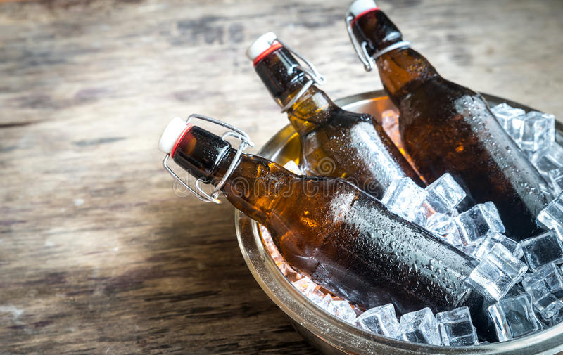 Bottles of beer in ice cubes. On the wooden background stock photography