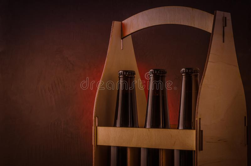 bottles of beer in a wooden box on a red light background/bottles of beer in a wooden box on a red light background. Selective royalty free stock photo